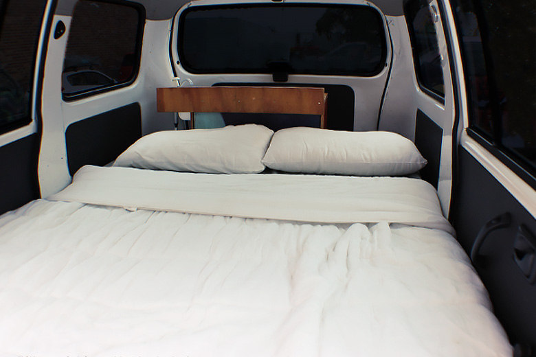 spacious campervan bed made up with white pillows and blankets